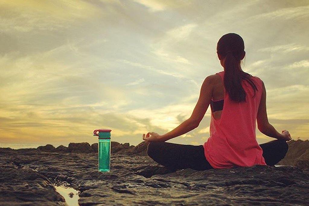 Dame gjør Yoga og bruker drikkeflasken fra Wow Gear