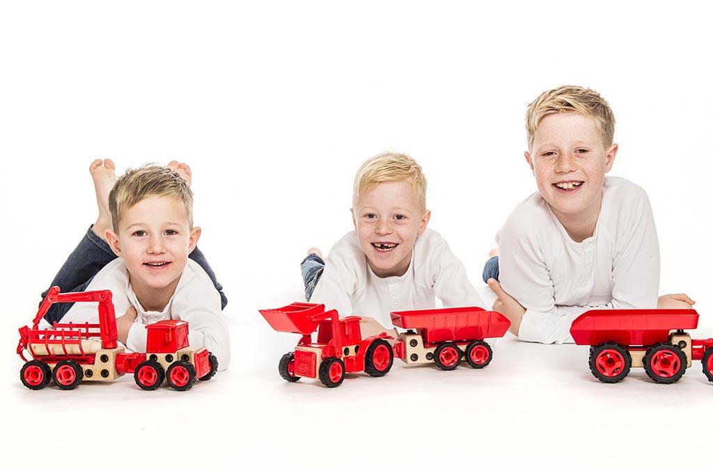 Tre barn ligger på gulvet og leker med traktorer