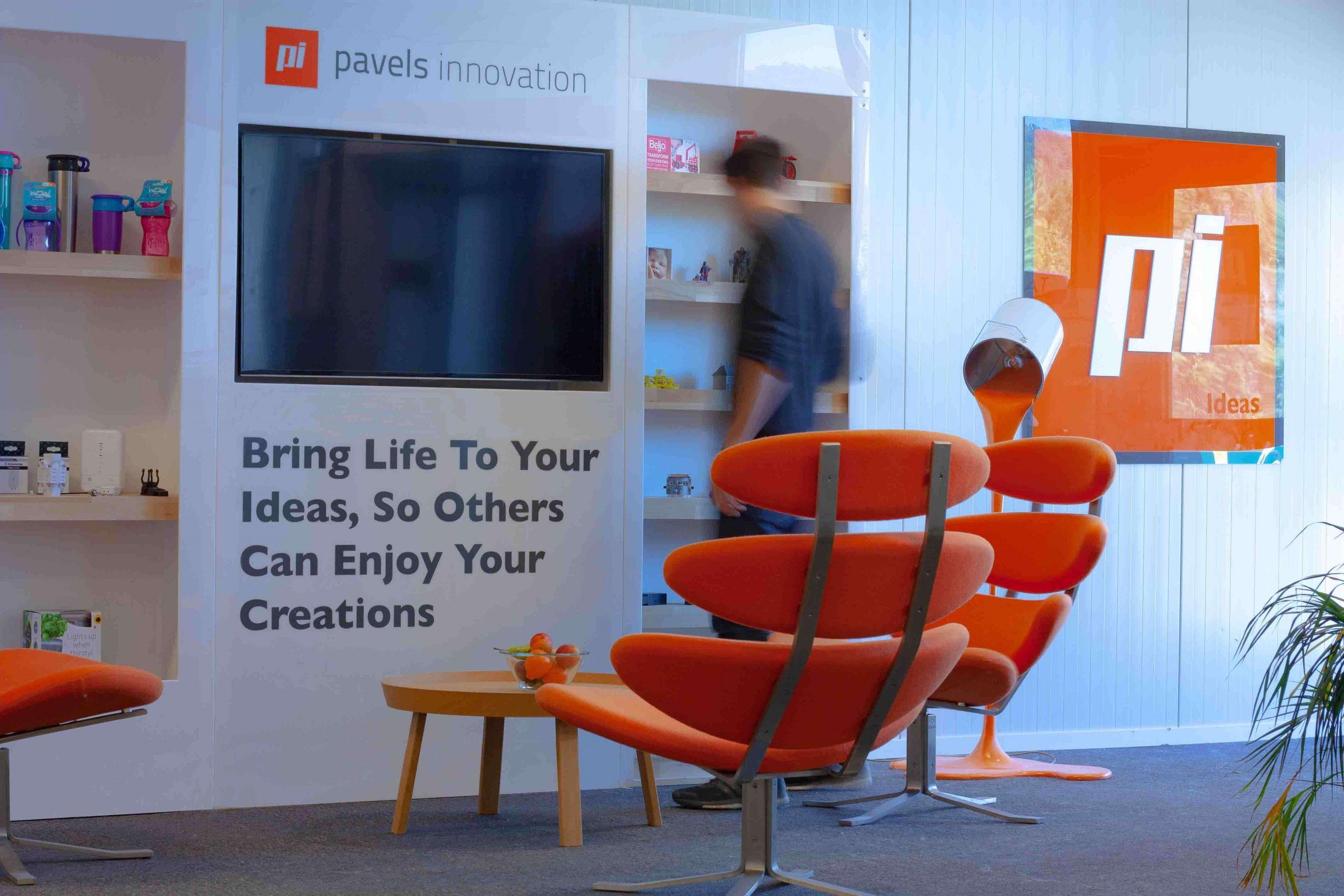 Bilde fra kontoret til Pavels Innovation. Sitat på veggen, oransj stol og logo på veggen.